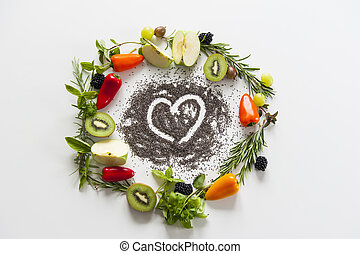 wreath of vegetables and fruits with heart from chia seeds on white background