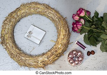 wreath, pink baubles, roses and silver gift box for the preparation of Christmas garland