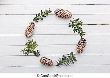Wreath with natural decorations hanging on a white wooden background