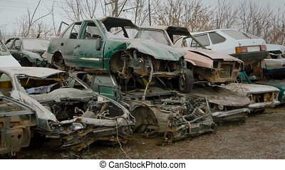 Wrecked vehicles are placed on top of one another on junkyard. Tons of metal scraps for recycling.