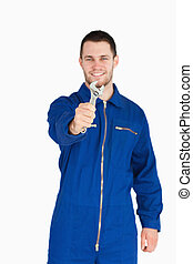 Wrench shown by smiling young mechanic in boiler suit