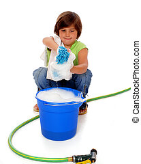 Squatting elementary girl wring a sudsy spong into a bucket of soapy water. Isolated on white.