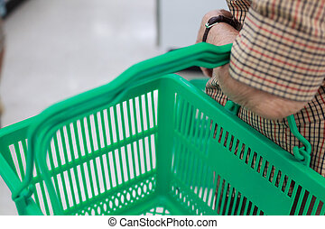 wrinkled elderly woman's hand holding shopping basket in shopping mall. Health care, Help, Support, Lifestyle, Senior Workforce, Activities concept.
