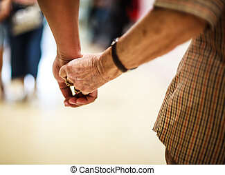 wrinkled elderly woman's hand holding to young man's hand, walking in shopping mall. Family Relation, Health, Help, Support, Insurance concept.