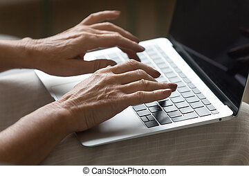 Wrinkled female hands typing message on laptop keyboard.
