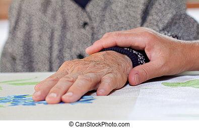 Wrinkled hands - Doctor's hand holding a wrinkled elderly...