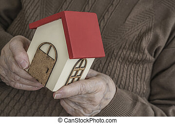 wrinkled hands holding a small model house