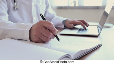 Wrinkled male hands writing information in medical ...