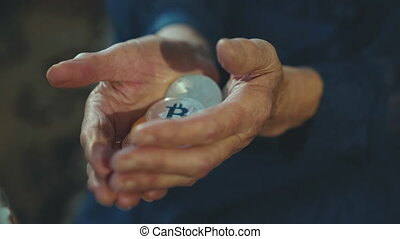 Wrinkled old female hands holding many golden and silver...