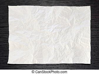 Wrinkled White paper on dark wood background