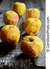 wrinkled yellow apples on a wooden