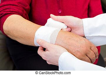 Wrist bandaging - Photo of doctor bandaging the elderly...