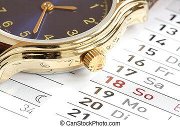 Wrist watch on the calendar background