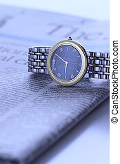 wrist  watch over newspaper
