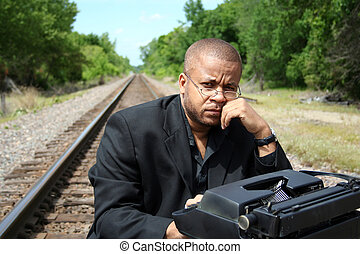 Young man with his typewriter on the train tracks.