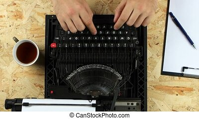 Writer typing text on a typewriter throws out a sheet. View...