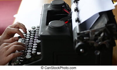 Writer writing on typewriter - Hand of a young woman writer...