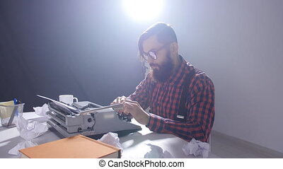 Writer's day concept. Young male writer in a dark room typing on a typewriter
