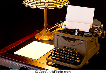 Old, antique, vintage, typewriter in writer's or author's area with lamp on black background