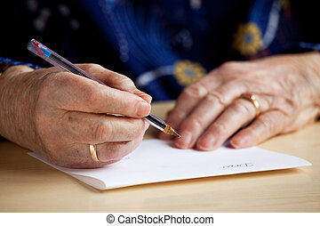 Writing a Letter - An old pair of hands writing a letter