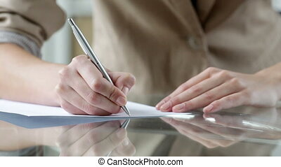 Close-up of a woman writing on a blank sheet of paper