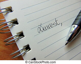 Writing a letter on lined paper beginning with Dear / Dearest