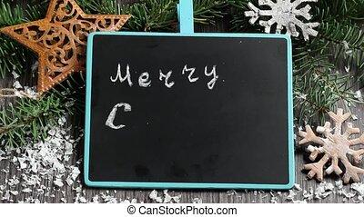 Writing Christmas greetings on black chalkboard