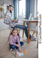 Writing daughter sitting on the floor, dad working at the table.