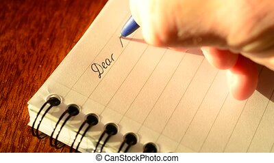 Writing DEAR MOM with a ballpoint pen in a notepad.