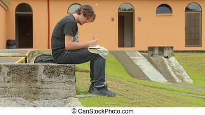 Man writing journal sitting in a park