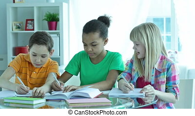 Writing essay - Diligent pupils helping each other while...