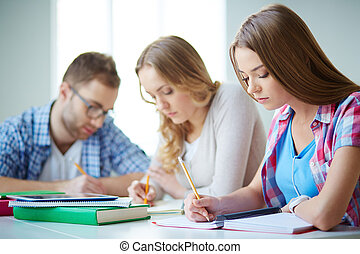 Writing essay - Smart girl carrying out written task with...