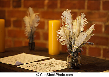 Writing. Feather quill pens, candle and old sheet of paper on wooden desk. Vintage retro style.