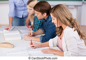 Writing Female Student With Classmates At Desk - Portrait of...