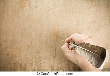 writing hand with pen feather at old wood background texture