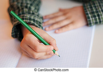 Writing homework - Child hand writing on a sheet of paper...