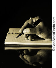 Writing in a notebook - Vintage vertical photo of a hand of...