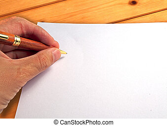 Male hand writing on a white paper, over wooden background