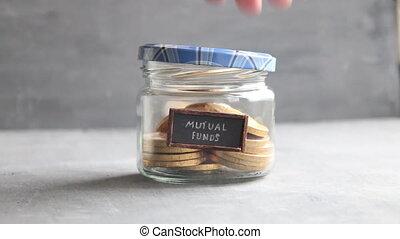 writing MUTUAL FUNDS, and money in jar - writing MUTUAL...