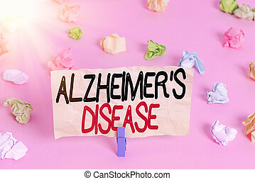 Writing note showing Alzheimers Disease. Business concept for irreversible brain disorder that slowly destroys memory Colored crumpled papers empty reminder pink floor background clothespin