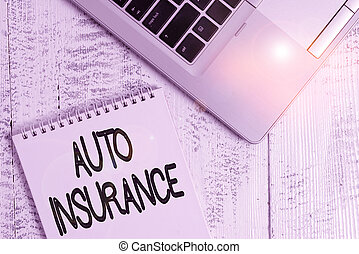 Writing note showing Auto Insurance. Business photo showcasing mitigate costs associated with getting into an auto accident Top trendy metallic laptop blank spiral notepad lying on wooden table.