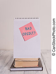 Writing note showing Bad Creditquestion. Business photo showcasing inabilityof a demonstrating to repay a debt on time and in full Stacked books spiral note book sticky lying vintage retro wooden table.