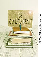 Writing note showing Be Consistent. Business concept for Uniform Persistent Firm Unalterable Even Unchanging Rapport pile stacked books notebook pin color reminder white wooden