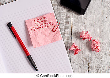 Writing note showing Brand Marketing. Business photo showcasing Creating awareness about products around the world Wrinkle paper notebook and stationary placed on wooden background.