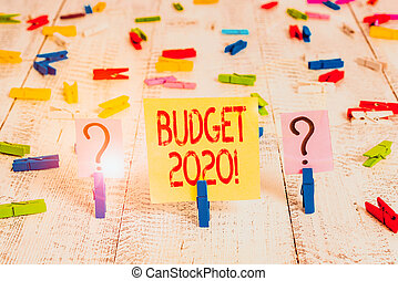 Writing note showing Budget 2020. Business photo showcasing estimate of income and expenditure for next or current year Crumbling sheet with paper clips placed on the wooden table.