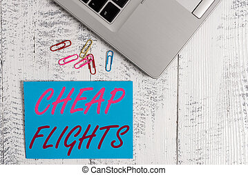 Writing note showing Cheap Flights. Business photo showcasing costing little money or less than is usual or expected airfare Trendy metallic laptop blank sticky note colored clips on vintage table.