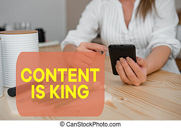 Writing note showing Content Is King. Business photo showcasing believe that content is central to the success of a website woman using smartphone and technological devices inside the home.