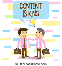 Writing note showing Content Is King. Business photo showcasing believe that content is central to the success of a website Two White Businessmen Colleagues with Brief Cases Sharing Idea Solution.