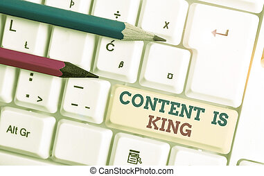 Writing note showing Content Is King. Business photo showcasing Content is the heart of todays marketing strategies White pc keyboard with note paper above the white background.