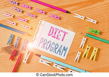 Writing note showing Diet Program. Business photo showcasing practice of eating food in a regulated and supervised fashion Colored clothespin papers empty reminder wooden floor background office.